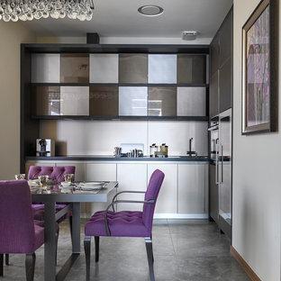 Идея дизайна: угловая кухня в современном стиле с обеденным столом, врезной раковиной, плоскими фасадами, серыми фасадами, техникой из нержавеющей стали, серым полом и белым фартуком без острова