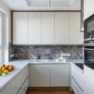 Пример оригинального дизайна: отдельная, п-образная кухня в современном стиле с монолитной раковиной, плоскими фасадами, белыми фасадами, серым фартуком, черной техникой, коричневым полом, белой столешницей, фартуком из цементной плитки и паркетным полом среднего тона без острова