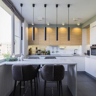 Свежая идея для дизайна: угловая кухня в современном стиле с одинарной раковиной, плоскими фасадами, белыми фасадами, белым фартуком, белой техникой, полуостровом, серым полом и белой столешницей - отличное фото интерьера