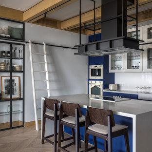 Пример оригинального дизайна: прямая кухня в стиле лофт с стеклянными фасадами, белым фартуком, техникой из нержавеющей стали, светлым паркетным полом, островом, белой столешницей, раковиной в стиле кантри, синими фасадами, бежевым полом и балками на потолке