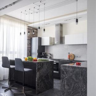 На фото: угловая кухня-гостиная среднего размера в современном стиле с гранитной столешницей, серым фартуком, фартуком из керамогранитной плитки, полом из керамогранита, островом, серым полом, плоскими фасадами, черными фасадами и черной столешницей