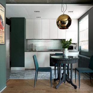Стильный дизайн: маленькая линейная кухня в современном стиле с обеденным столом, белыми фасадами, накладной раковиной, плоскими фасадами, фартуком цвета металлик и паркетным полом среднего тона - последний тренд