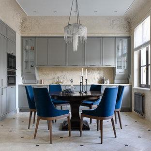 Bild på ett avskilt vintage beige beige l-kök, med luckor med infälld panel, grå skåp, beige stänkskydd, svarta vitvaror, travertin golv och beiget golv