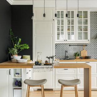 Стильный дизайн: параллельная кухня в скандинавском стиле с фасадами с выступающей филенкой, белыми фасадами, деревянной столешницей, разноцветным фартуком, техникой под мебельный фасад, светлым паркетным полом, полуостровом, бежевым полом и коричневой столешницей - последний тренд