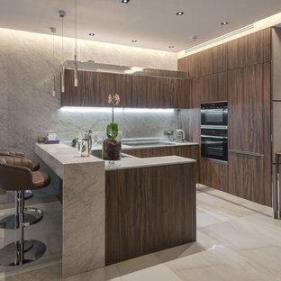 Новый формат декора квартиры: п-образная кухня-гостиная в современном стиле с накладной раковиной, плоскими фасадами, темными деревянными фасадами, серым фартуком, техникой из нержавеющей стали, полуостровом, бежевым полом и серой столешницей