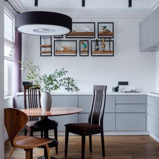 Пример оригинального дизайна: угловая кухня среднего размера в современном стиле с обеденным столом, плоскими фасадами, серыми фасадами, техникой под мебельный фасад, паркетным полом среднего тона, коричневым полом и белой столешницей без острова