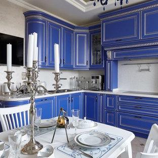 Стильный дизайн: отдельная, угловая кухня в классическом стиле с накладной раковиной, фасадами с выступающей филенкой, синими фасадами и бежевым фартуком без острова - последний тренд