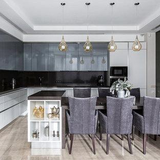 Стильный дизайн: отдельная, угловая кухня в современном стиле с плоскими фасадами, серыми фасадами, черным фартуком, островом, бежевым полом и черной столешницей - последний тренд
