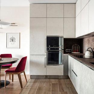 Стильный дизайн: угловая кухня в современном стиле с обеденным столом, плоскими фасадами, серыми фасадами, черной техникой, паркетным полом среднего тона и коричневым полом - последний тренд