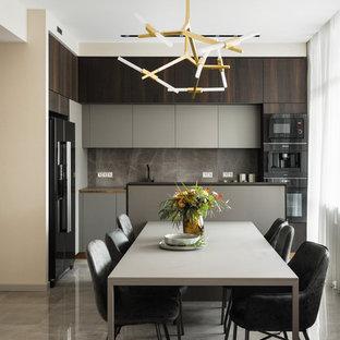 Пример оригинального дизайна: угловая кухня среднего размера в современном стиле с обеденным столом, плоскими фасадами, серыми фасадами, серым фартуком, фартуком из керамогранитной плитки, черной техникой, полом из керамогранита, серым полом, серой столешницей, накладной раковиной и островом