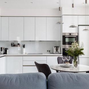 Идея дизайна: угловая кухня-гостиная со шкафом над холодильником в современном стиле с врезной раковиной, плоскими фасадами, белыми фасадами, белым фартуком, техникой из нержавеющей стали и белой столешницей без острова