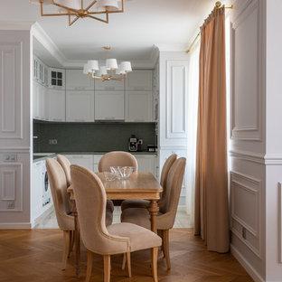 На фото: п-образная кухня в классическом стиле с обеденным столом и белыми фасадами без острова с