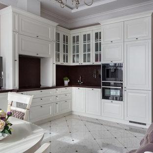 Удачное сочетание для дизайна помещения: угловая кухня-гостиная в стиле современная классика с фасадами с выступающей филенкой, белыми фасадами, коричневым фартуком, черной техникой, белым полом и коричневой столешницей без острова - самое интересное для вас