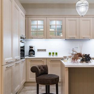 На фото: угловая кухня среднего размера в современном стиле с фасадами с утопленной филенкой, бежевыми фасадами, техникой под мебельный фасад, островом, серым полом и белой столешницей