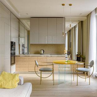 Идея дизайна: маленькая угловая кухня-гостиная в современном стиле с плоскими фасадами, серыми фасадами, техникой из нержавеющей стали, светлым паркетным полом, бежевым полом, бежевой столешницей, накладной раковиной и бежевым фартуком без острова