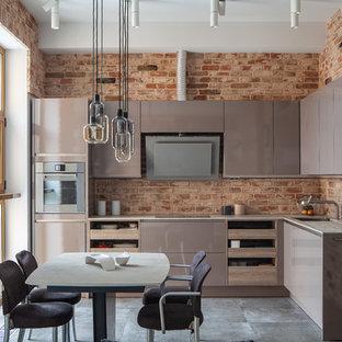 На фото: угловая кухня в стиле лофт с обеденным столом, врезной раковиной, плоскими фасадами, коричневыми фасадами и серым полом без острова