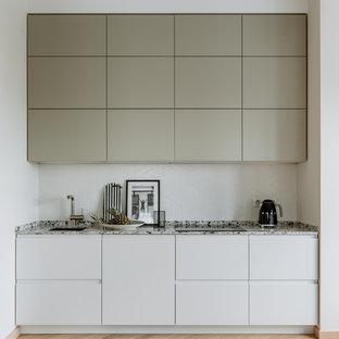 Пример оригинального дизайна: маленькая прямая кухня в современном стиле с плоскими фасадами, белым фартуком, светлым паркетным полом и бежевым полом