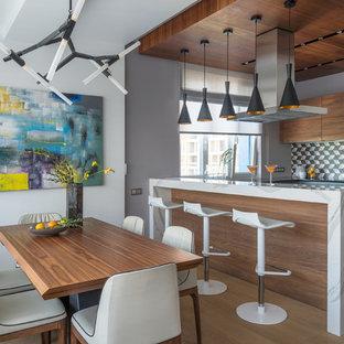 Создайте стильный интерьер: п-образная кухня в современном стиле с плоскими фасадами, фасадами цвета дерева среднего тона, разноцветным фартуком, темным паркетным полом, полуостровом, черной столешницей и коричневым полом - последний тренд