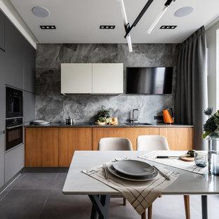 Создайте стильный интерьер: угловая кухня в современном стиле с врезной раковиной, плоскими фасадами, белыми фасадами, столешницей из акрилового камня, серым фартуком, фартуком из керамогранитной плитки, черной техникой, полом из керамогранита, серым полом и серой столешницей - последний тренд