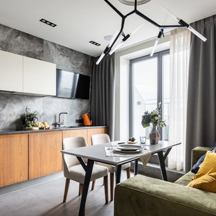 Design ideas for a contemporary l-shaped kitchen in Saint Petersburg with an undermount sink, flat-panel cabinets, white cabinets, solid surface benchtops, grey splashback, porcelain splashback, black appliances, porcelain floors, grey floor and grey benchtop.