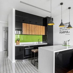 Идея дизайна: параллельная кухня-гостиная среднего размера в современном стиле с врезной раковиной, плоскими фасадами, черными фасадами, столешницей из акрилового камня, зеленым фартуком, фартуком из стекла, полом из керамогранита, полуостровом, серым полом и черной техникой