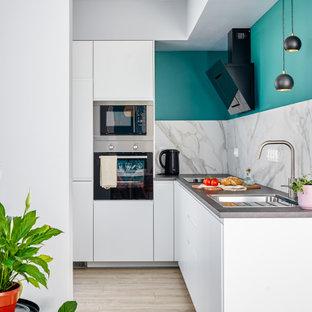 На фото: угловая кухня в скандинавском стиле с врезной раковиной, плоскими фасадами, белыми фасадами, белым фартуком, фартуком из каменной плиты, техникой из нержавеющей стали, светлым паркетным полом, бежевым полом и серой столешницей