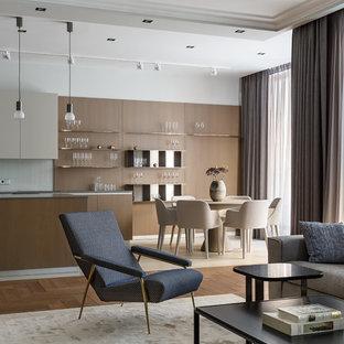 На фото: линейная кухня-гостиная в современном стиле с плоскими фасадами и островом с