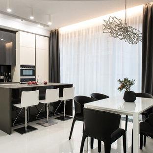 На фото: линейная кухня в современном стиле с плоскими фасадами, белыми фасадами, черным фартуком, черной техникой, островом, белым полом и черной столешницей с