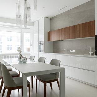 Стильный дизайн: линейная кухня среднего размера в современном стиле с обеденным столом, врезной раковиной, плоскими фасадами, белыми фасадами, серым фартуком, фартуком из керамогранитной плитки, черной техникой, полом из керамогранита, серым полом и белой столешницей без острова - последний тренд