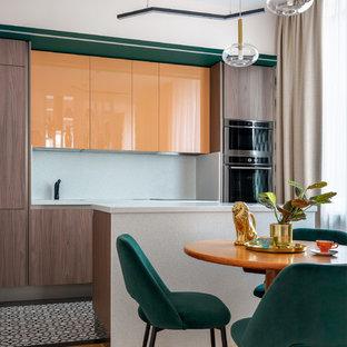 Пример оригинального дизайна: линейная кухня в современном стиле с обеденным столом, плоскими фасадами, оранжевыми фасадами, белым фартуком, островом, разноцветным полом, белой столешницей и техникой из нержавеющей стали