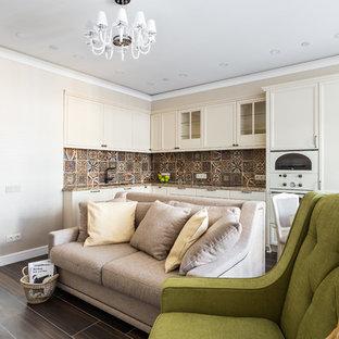 На фото: угловая кухня-гостиная в стиле современная классика с фасадами с утопленной филенкой, бежевыми фасадами, коричневым фартуком, белой техникой и коричневым полом без острова
