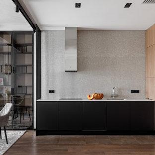 Стильный дизайн: угловая кухня-гостиная в современном стиле с врезной раковиной, плоскими фасадами, черными фасадами, серым фартуком, техникой из нержавеющей стали, коричневым полом и белой столешницей без острова - последний тренд