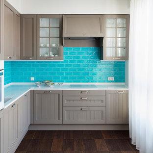 На фото: угловая кухня в современном стиле с монолитной раковиной, серыми фасадами, синим фартуком, белой техникой, коричневым полом, фасадами в стиле шейкер, фартуком из плитки кабанчик и темным паркетным полом без острова с