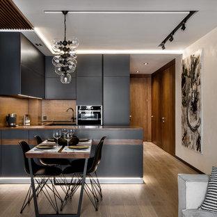 Источник вдохновения для домашнего уюта: п-образная кухня среднего размера в современном стиле с обеденным столом, врезной раковиной, плоскими фасадами, серыми фасадами, деревянной столешницей, коричневым фартуком, фартуком из дерева, паркетным полом среднего тона, полуостровом, черной техникой, коричневым полом и коричневой столешницей