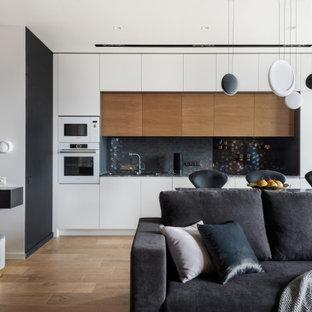 На фото: прямая кухня-гостиная в современном стиле с плоскими фасадами, белыми фасадами, черным фартуком, белой техникой, коричневым полом и черной столешницей с