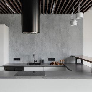 На фото: п-образная кухня в современном стиле с накладной раковиной, плоскими фасадами, белыми фасадами, серым фартуком, полуостровом и серой столешницей с