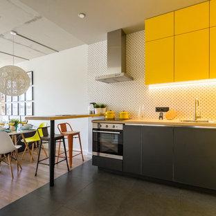 Новые идеи обустройства дома: угловая кухня-гостиная в современном стиле с накладной раковиной, плоскими фасадами, желтыми фасадами, столешницей из дерева, белым фартуком, техникой из нержавеющей стали, черным полом и бежевой столешницей без острова