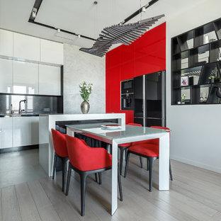 Moderne Wohnküche in L-Form mit flächenbündigen Schrankfronten, roten Schränken, Küchenrückwand in Schwarz, schwarzen Elektrogeräten, hellem Holzboden, Kücheninsel, beigem Boden und weißer Arbeitsplatte in Moskau