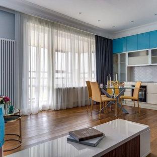 Пример оригинального дизайна: кухня среднего размера в современном стиле с плоскими фасадами, синими фасадами, белым фартуком, черной техникой и коричневым полом