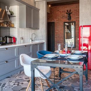 Пример оригинального дизайна: линейная кухня в стиле лофт с обеденным столом, накладной раковиной, серыми фасадами, белым фартуком, техникой из нержавеющей стали, фасадами в стиле шейкер и серым полом без острова
