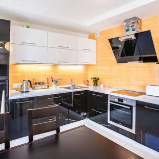 На фото: угловые кухни в современном стиле с обеденным столом, накладной раковиной, плоскими фасадами, черными фасадами и техникой из нержавеющей стали без острова