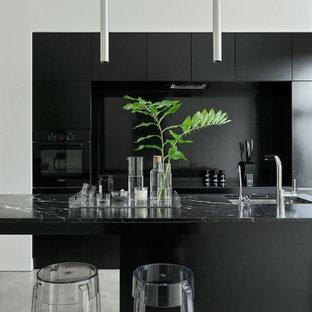 Неиссякаемый источник вдохновения для домашнего уюта: большая параллельная кухня в современном стиле с врезной раковиной, плоскими фасадами, черными фасадами, черным фартуком, черной техникой, островом, серым полом и черной столешницей