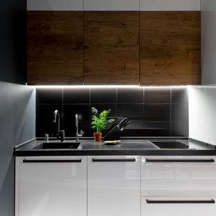 Пример оригинального дизайна интерьера: линейная кухня среднего размера в современном стиле с плоскими фасадами, белыми фасадами, черным фартуком, черной столешницей, монолитной раковиной, обеденным столом, столешницей из акрилового камня, фартуком из керамической плитки, белой техникой, полом из керамической плитки и разноцветным полом без острова
