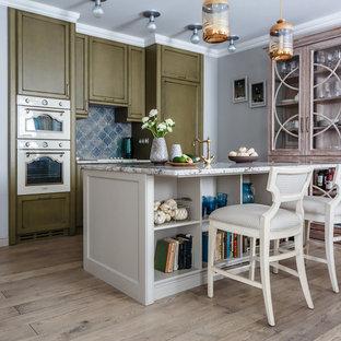 На фото: линейная кухня в стиле современная классика с обеденным столом, фасадами с утопленной филенкой, зелеными фасадами, синим фартуком, белой техникой, островом, раковиной в стиле кантри, паркетным полом среднего тона и коричневым полом с