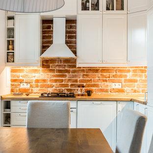 Стильный дизайн: маленькая угловая кухня-гостиная в современном стиле с белыми фасадами, коричневым фартуком и фартуком из кирпича без острова - последний тренд