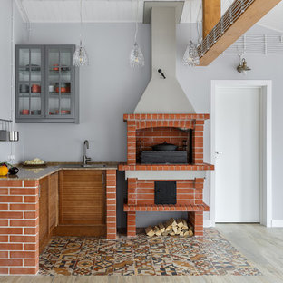 Свежая идея для дизайна: угловая кухня-гостиная в стиле кантри с фасадами с филенкой типа жалюзи, фасадами цвета дерева среднего тона, серым фартуком, разноцветным полом и коричневой столешницей без острова - отличное фото интерьера