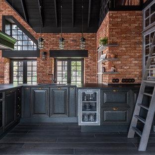 Идея дизайна: большая п-образная кухня-гостиная в стиле лофт с врезной раковиной, фасадами с утопленной филенкой, черными фасадами, техникой под мебельный фасад, черным полом и черной столешницей без острова