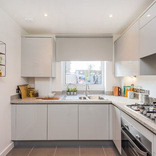 This is an example of a contemporary l-shaped enclosed kitchen in London with a built-in sink, flat-panel cabinets, white cabinets, granite worktops, metallic splashback, metal splashback, stainless steel appliances, no island, grey floors and beige worktops.