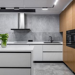 Источник вдохновения для домашнего уюта: кухня в современном стиле с накладной раковиной, плоскими фасадами, белыми фасадами, серым фартуком, фартуком из стекла, черной техникой, островом, серым полом и белой столешницей