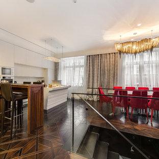 На фото: параллельные кухни - столовые в современном стиле с плоскими фасадами, белыми фасадами, белым фартуком, белой техникой, темным паркетным полом, островом, коричневым полом и белой столешницей